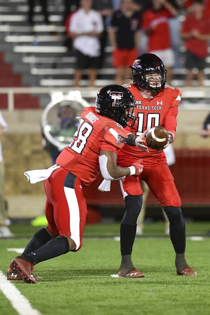 Texas Tech quarterback Alan Bowman (10) hands off to running back Tahj Brooks (28) during the second half of an NCAA college football game in Lubbock, Texas, Saturday, Nov. 14, 2020. (AP Photo/Justin Rex)