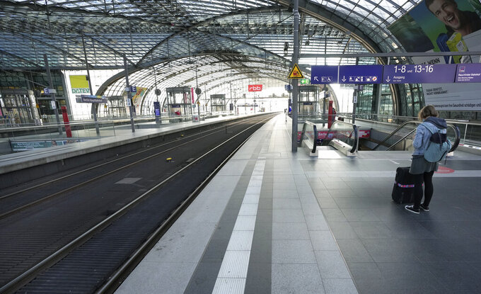 A person stands on the empty station platform at the main station in Berlin, Germany, Wednesday, Aug. 11, 2021. A nationwide, two-day train strike has brought big parts of the German railway and commuter system to a standstill. (AP Photo/Michael Sohn)