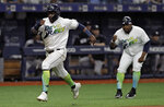 Tampa Bay Rays' Guillermo Heredia, left, gets advice from third base coach Rodney Linares as he scores on a single by Ji-Man Choi during the sixth inning of a baseball game against the New York Yankees on Saturday, May 11, 2019, in St. Petersburg, Fla. (AP Photo/Chris O'Meara)
