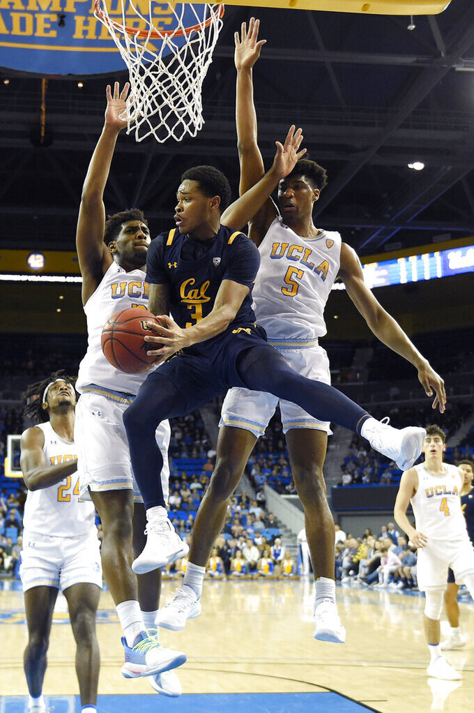 California guard Paris Austin, center, passes the ball as UCLA forward Cody Riley, second from left, and guard Chris Smith, right, defend during the second half of an NCAA college basketball game Sunday, Jan. 19, 2020, in Los Angeles. UCLA won 50-40. (AP Photo/Mark J. Terrill)