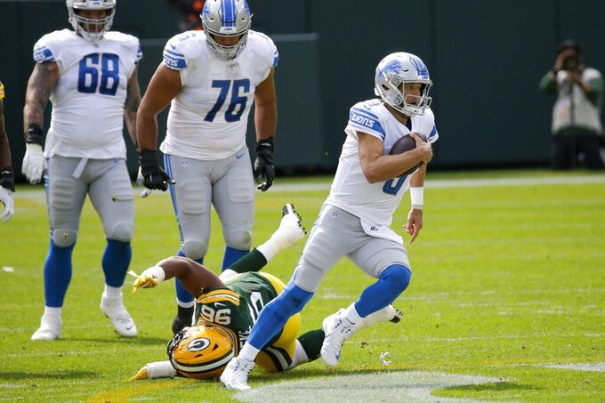 Detroit Lions' Matthew Stafford runs for a first down during the first half of an NFL football game against the Green Bay Packers Sunday, Sept. 20, 2020, in Green Bay, Wis. (AP Photo/Mike Roemer)