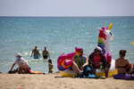 FILE - In this Monday, June 7, 2021 file photo, tourists sunbathe on the beach at the Spanish Balearic Island of Mallorca, Spain. Europe is opening up to Americans and other visitors after more than a year of COVID-induced restrictions. European governments hope to lure back tourists - and their dollars - back to the continent's trattorias, vistas and cultural treasures. (AP Photo/Francisco Ubilla, FIle)