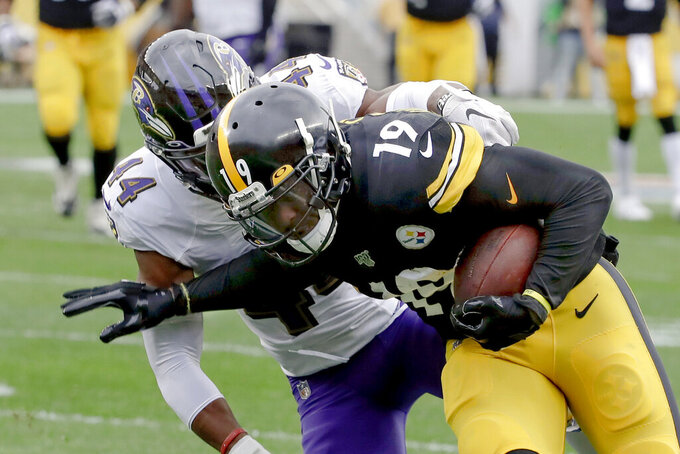 Pittsburgh Steelers wide receiver JuJu Smith-Schuster (19) gets away from Baltimore Ravens cornerback Marlon Humphrey (44) on his way to scoring a touchdown in the first half of an NFL football game, Sunday, Oct. 6, 2019, in Pittsburgh. (AP Photo/Don Wright)