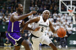 Michigan State guard Cassius Winston (5) drives on Albion forward Quinton Armstrong during the second half of an NCAA college exhibition basketball game, Tuesday, Oct. 29, 2019, in East Lansing, Mich. (AP Photo/Carlos Osorio)