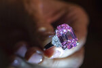 A Christie's employee displays an 18.96-carat fancy vivid pink diamond during a preview at Christie's in Geneva, Switzerland, Thursday, Nov. 8, 2018. It is estimated to sell between $30-$50 million. The auction will take place in Geneva, on Nov. 13. (Martial Trezzini/Keystone via AP)