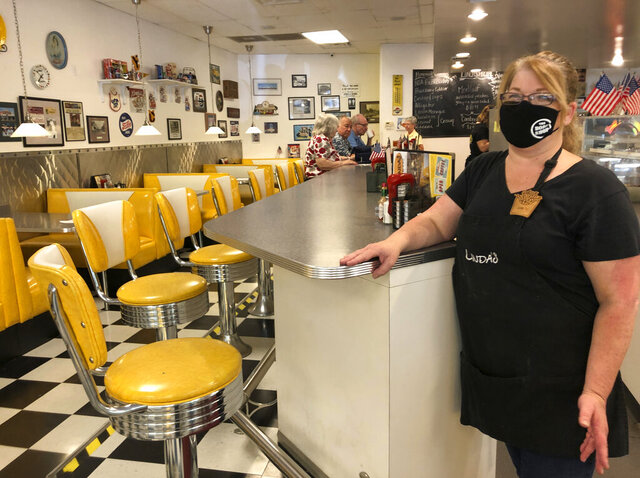 Restaurant manager Lori Pack stands at the counter of Linda's Soda Bar and Grill in Yuba City, Calif., Thursday, July 9, 2020. Sutter County was one of the first counties to reopen its economy when it defied Gov. Gavin Newsom's stay-at-home order in May to allow restaurants, hair salons, gyms and shopping malls to reopen. But Thursday, the county was added to a state watch list because of its rising number of coronavirus cases and hospitalizations. That will eventually trigger another round of restrictions, forcing bars to close and indoor operations to cease at restaurants and other public places for three weeks. Pack says the restaurant tried takeout-only service for three weeks earlier this year during the coronavirus pandemic. But she said it was