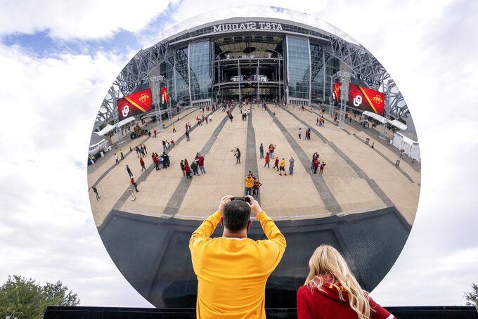 "Brian and Marcia Sheriff, of Des Moines, Iowa, take a picture of themselves in the ""Sky Mirror"" sculpture outside AT&T Stadium before an NCAA college football game between Iowa State and Oklahoma for the Big 12 Conference championship, Saturday, Dec. 19, 2020, in Arlington, Texas. (AP Photo/Jeffrey McWhorter)"