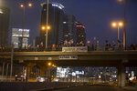 Israeli protesters hold flags and signs as they stand on a bridge to demonstrate against Israel's Prime Minister Benjamin Netanyahu in Tel Aviv, Israel, Saturday, Aug. 8, 2020. Hebrew reads: