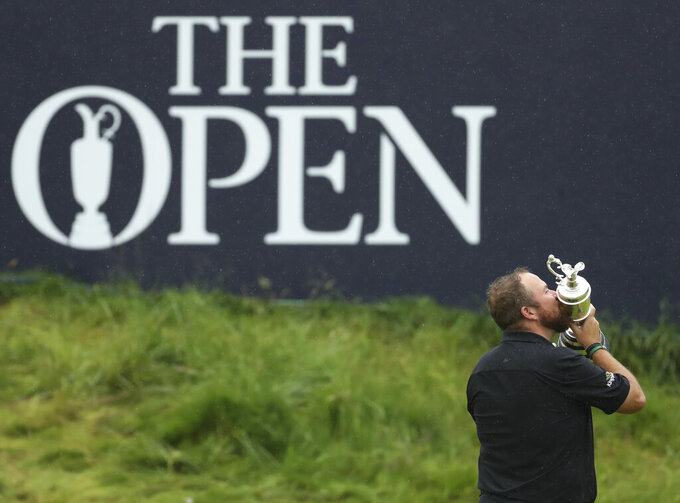 FILE - In this file photo dated Sunday, July 21, 2019, Ireland's Shane Lowry holds the Claret Jug trophy after winning the British Open Golf Championships at Royal Portrush in Northern Ireland.  The R&A announced Monday Dec. 7, 2020, that the British Open will be played at Royal Liverpool in 2023 and at Royal Troon in 2024, after the 2020 Championships were cancelled due to the coronavirus pandemic. (AP Photo/Peter Morrison, FILE)