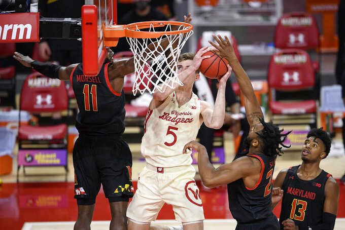 Wisconsin forward Tyler Wahl (5) goes to the basket against Maryland guard Darryl Morsell (11), guard Hakim Hart (13) and forward Donta Scott (24) during the first half of an NCAA college basketball game Wednesday, Jan. 27, 2021, in College Park, Md. (AP Photo/Nick Wass)