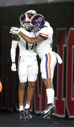 Virginia's Ra'Shaun Henry (17) and Terrell Jana (13) celebrate a play in the first half of an NCAA college football game against Miami in Miami Gardens, Fla., Saturday, Oct. 24, 2020. (Al Diaz/Miami Herald via AP)