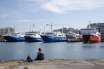 A fisherman sits on the dock during a 24-hour labor strike at the port of Piraeus, near Athens, Wednesday, June 16, 2021. Greece's biggest labor unions staged a 24-hour strike to protest a labor bill being voted in parliament. (AP Photo/Petros Giannakouris)