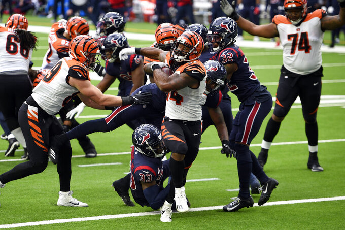 Cincinnati Bengals running back Samaje Perine (34) runs for a touchdown as Houston Texans' A.J. Moore Jr. (33) and Zach Cunningham try to tackle him during the second half of an NFL football game Sunday, Dec. 27, 2020, in Houston. (AP Photo/Eric Christian Smith)