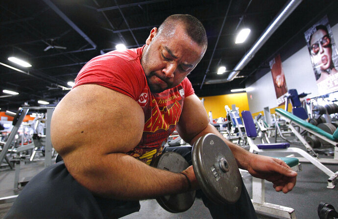 In this Nov. 16, 2012, file photo, Egyptian body builder Moustafa Ismail lifts free weights during his daily workout in Milford, Mass. On Monday, April 22, 2019, Merriam-Webster added the definition of swole to it's online dictionary, with the meaning