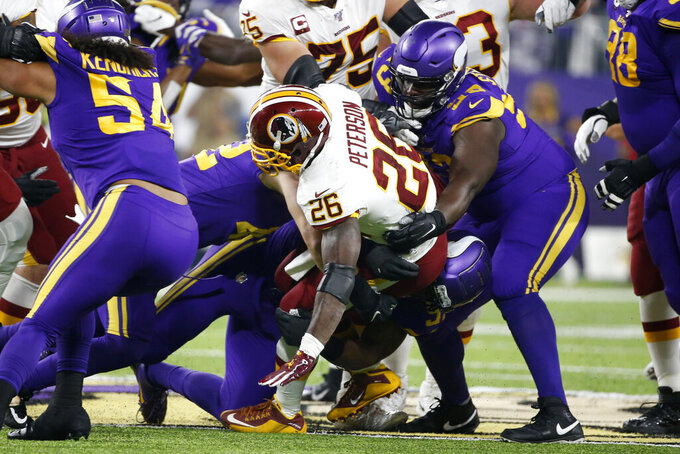 Washington Redskins running back Adrian Peterson (26) is tackled by Minnesota Vikings defensive tackle Shamar Stephen, right, during the first half of an NFL football game, Thursday, Oct. 24, 2019, in Minneapolis. (AP Photo/Bruce Kluckhohn)