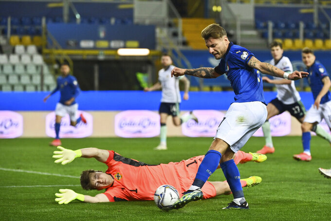 FILE - In this Thursday, March 25, 2021 filer, Italy's Ciro Immobile, right, competes for the ball with Northern Ireland's goalkeeper Bailey Peacock Farrell, bottom, during the World Cup 2022 qualifier group c soccer game between Italy and Northern Ireland at the Stadio Ennio Tardini in Parma, Italy. (Massimo Paolone/LaPresse via AP, File )