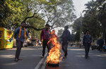 Indian students burn car tires during a shutdown protest against the Citizenship Amendment Bill (CAB) in Gauhati, India, Tuesday, Dec. 10, 2019. Opponents of legislation that would grant Indian citizenship to non-Muslim illegal migrants from Pakistan, Bangladesh and Afghanistan have enforced an 11-hour shutdown across India's northeastern region. (AP Photo/Anupam Nath)