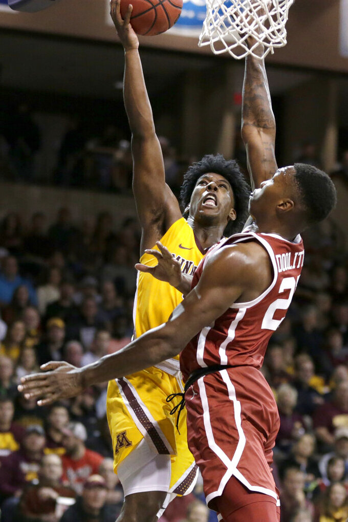 Minnesota's Marcus Carr (5) goes for a basket against Oklahoma's Kristian Doolittle (21) during the second half of an NCAA college basketball game in Sioux Falls, S.D., Saturday, Nov. 9, 2019. (AP Photo/Nati Harnik)