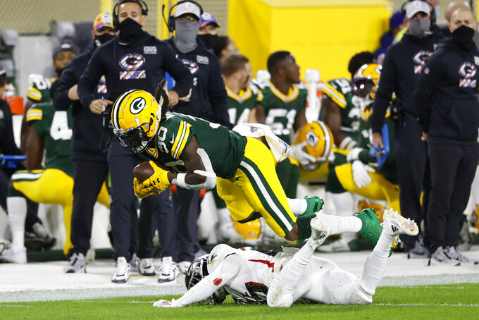 Green Bay Packers' Jamaal Williams (30) is tackled by Atlanta Falcons' Damontae Kazee (27) during the first half of an NFL football game, Monday, Oct. 5, 2020, in Green Bay, Wis. (AP Photo/Tom Lynn)