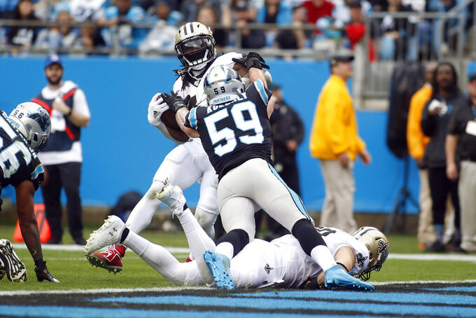 New Orleans Saints running back Alvin Kamara runs the ball for a touchdown as Carolina Panthers middle linebacker Luke Kuechly (59) tyries to tackle during the first half of an NFL football game in Charlotte, N.C., Sunday, Dec. 29, 2019. (AP Photo/Brian Blanco)