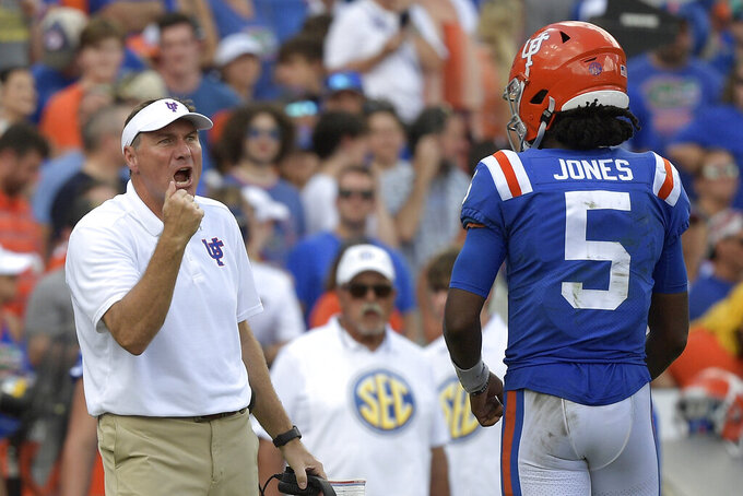 Florida head coach Dan Mullen, left, calls out instructions in front of quarterback Emory Jones (5) during the second half of an NCAA college football game against Vanderbilt, Saturday, Oct. 9, 2021, in Gainesville, Fla. (AP Photo/Phelan M. Ebenhack)