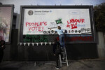 Young members of Britain's opposition Labour party write on a billboard why they want Jeremy Corbyn the party leader to back a