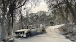 """Charred remnants of vehicles sit in the driveway of Porfirio """"Pete"""" Reyna's Rumford Court home in Chicago Park where everything, including his home were a total loss due to the River Fire. Reyna, like others have already begun looking at rebuilding, Aug. 7, 2021. (Elias Funez/The Union via AP)"""