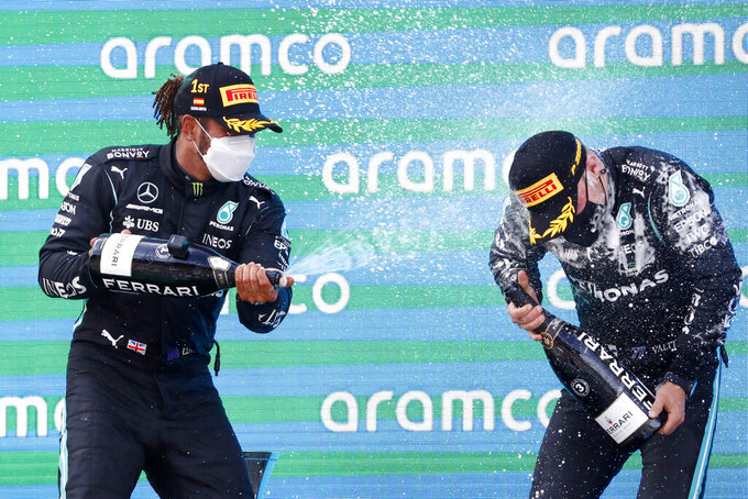 Winner Mercedes driver Lewis Hamilton of Britain, left, celebrates with third placed Mercedes driver Valtteri Bottas of Finland, right, on the podium of the Spanish Formula One Grand Prix at the Barcelona Catalunya racetrack in Montmelo, just outside Barcelona, Spain, Sunday, May 9, 2021. (AP Photo/Joan Monfort)