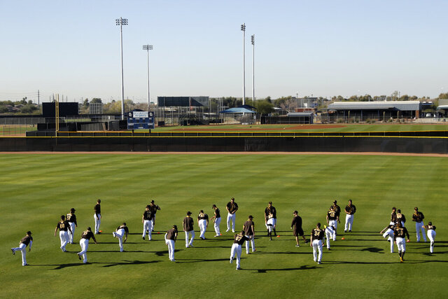 San Diego Padres players stretch during spring training baseball practice Saturday, Feb. 15, 2020, in Peoria, Ariz. (AP Photo/Charlie Riedel)