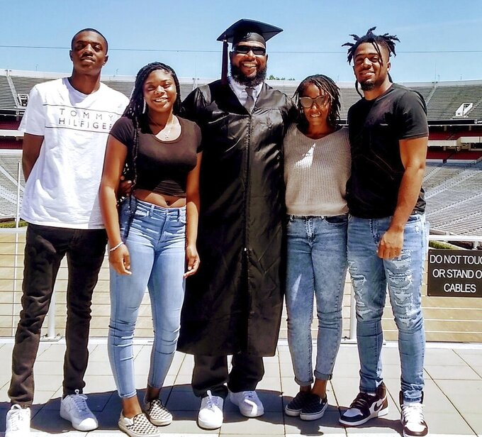 In this May 9, 2020, photo provided by Shedrick Wynn, Shedrick Wynn, center, poses in his cap and gown outside Sanford Stadium in Athens Ga. Wynn finally got his degree this semester, nearly 20 years after his playing career ended in 2002. Left to the right: Cayden Barnes, Destiny Browner, Shedrick Wynn, Andrea Wynn and Jalen Jackson. (Shedrick Wynn via AP)