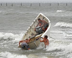 Fishermen launch a boat as they attempt to recover their haul-seine fishing net, Thursday, Sept. 13, 2018, in Virginia Beach, Va., as Hurricane Florence moves towards the eastern shore. (AP Photo/Alex Brandon)