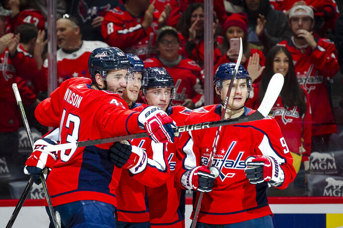 Washington Capitals left wing Jakub Vrana (13), of the Czech Republic, center Lars Eller (20), of Denmark, left wing Jakub Vrana (13), of the Czech Republic, and defenseman Dmitry Orlov (9), of Russia, celebrate Eller's goal during the third period of an NHL hockey game Sunday, Nov. 3, 2019, in Washington. The Capitals won 4-2. (AP Photo/Al Drago)