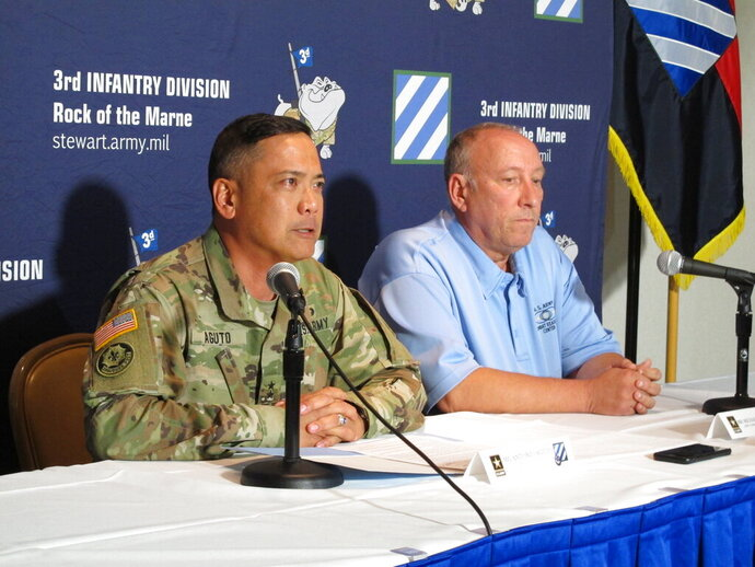 Army Maj. Gen. Antonio Aguto, left, and Army accident investigator Michael Barksdale hold a news conference, Monday, Oct. 21, 2019, at Fort Stewart, Ga., about a training accident that killed three soldiers and injured three others. Aguto said the soldiers' armored vehicle rolled off a bridge and landed upside down in a stream during a training exercise being conducted before dawn the day before. The cause of the fatal crash is being investigated. (AP Photo/Russ Bynum)