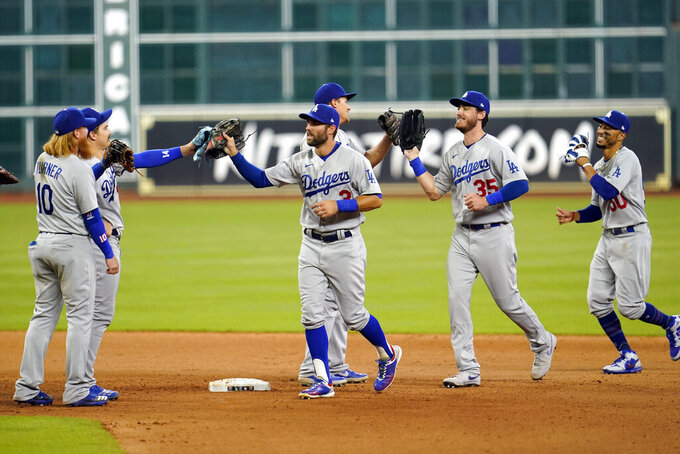 Los Angeles Dodgers' Chris Taylor (3), Cody Bellinger (35) and Mookie Betts (50) celebrate with teammates after a baseball game against the Houston Astros Wednesday, July 29, 2020, in Houston. The Dodgers won 4-2 in 13 innings. (AP Photo/David J. Phillip)