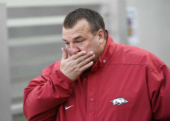 FILE - In this Nov. 24, 2017 file photo, Arkansas coach Bret Bielema wipes away tears as the senior players are introduced for the team's NCAA college football game against Missouri in Fayetteville, Ark.  Bielema is returning to the Big Ten and his home state to coach Illinois. Illinois hired the former Wisconsin and Arkansas coach, hoping he can turn around a program with nine straight losing seasons.  (AP Photo/Michael Woods)