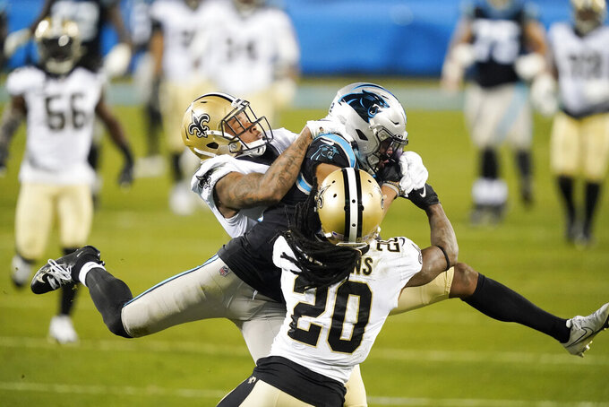 Carolina Panthers wide receiver D.J. Moore catches a pass between New Orleans Saints cornerback P.J. Williams and cornerback Janoris Jenkins (20) during the first half of an NFL football game Sunday, Jan. 3, 2021, in Charlotte, N.C. (AP Photo/Gerry Broome)