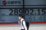 A man wearing a protective mask walks in front of an electronic stock board showing Japan's Nikkei 225 index at a securities firm Wednesday, June 9, 2021, in Tokyo. (AP Photo/Eugene Hoshiko)