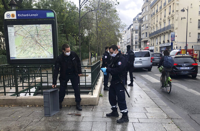 Police officers stand by a knife, seen on the ground, in Paris, Friday, Sept. 25, 2020. French terrorism authorities are investigating a knife attack that wounded at least two people Friday near the former offices of the satirical newspaper Charlie Hebdo in Paris, authorities said. A suspect has been arrested. (Soufian Fezzani Via AP)