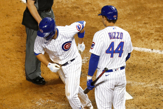 Chicago Cubs' Anthony Rizzo (44) greets Kris Bryant at home after Bryant's home run during the seventh inning of a baseball game against the Kansas City Royals Monday, Aug. 3, 2020, in Chicago. (AP Photo/Charles Rex Arbogast)
