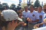 A crowd gathers as New York Gov. Andrew Cuomo prepares to eat a sausage at the New York State fairgrounds on Wednesday, Aug. 21, 2019, in Syracuse, N.Y. Richard Ball, commissioner for the state Department of Agriculture and Markets announced Wednesday that the state fair will be solely powered by renewable energy by 2023.  (AP Photo/Ryan Tarinelli)