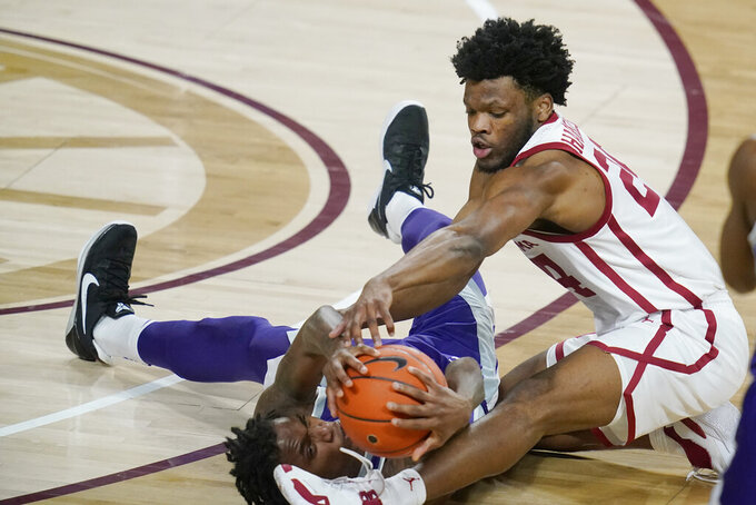 Oklahoma guard Elijah Harkless, right, and Kansas State guard DaJuan Gordon reach for the ball during the first half of an NCAA college basketball game Tuesday, Jan. 19, 2021, in Norman, Okla. (AP Photo/Sue Ogrocki)