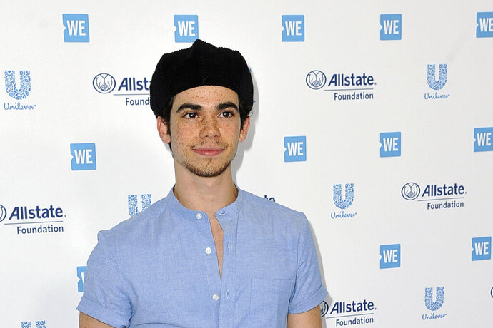 """FILE - In this April 25, 2019, file photo, Cameron Boyce arrives at WE Day California at The Forum in Inglewood, Calif. Actor Cameron Boyce, known for his roles in the Disney Channel franchise """"Descendants"""" and the Adam Sandler """"Grown Ups"""" movies, died Saturday, July 6, 2019, at his home in Los Angeles, according to his spokesperson. He was 20. (Photo by Richard Shotwell/Invision/AP, File)"""