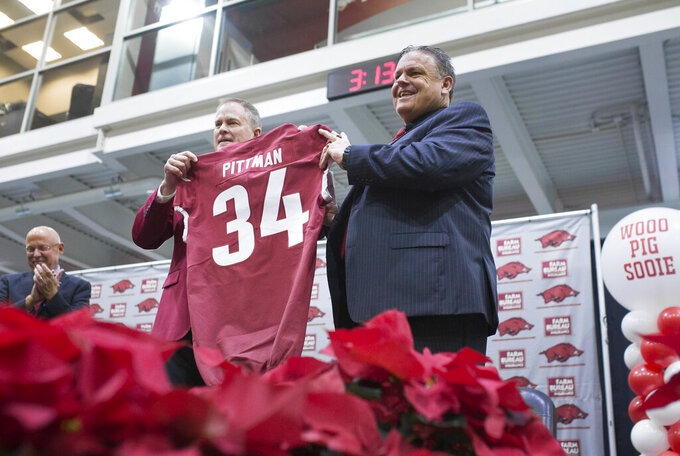 Coach Sam Pittman, right, and Hunter Yurachek, director of athletics, pose for pictures Monday, Dec. 9, 2019 in Fayetteville, Ark. Arkansas introduced former Georgia assistant Sam Pittman as its new head football coach. Pittman had a previous stop as an assistant with the Razorbacks and has spent much of his coaching career in the SEC. (Charlie Kaijo/The Northwest Arkansas Democrat-Gazette via AP)