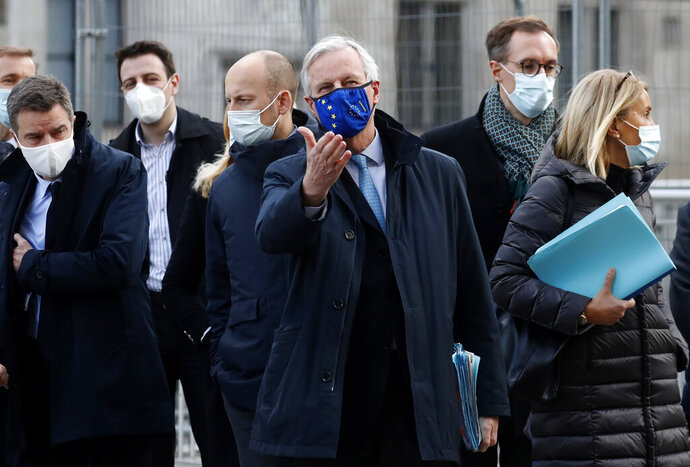 """FILE - In this file photo dated  Thursday, Nov. 12, 2020, European Commission's Head of Task Force for Relations with the United Kingdom Michel Barnier, centre, leaves the Conference Centre in London with unidentified members of his team.  The Brexit trade negotiations have been suspended Thursday Nov. 19, 2020, at a crucial stage because an EU negotiator has tested positive for the coronavirus and EU chief negotiator Michel Barnier said that """"we have decided to suspend the negotiations at our level for a short period.""""  (AP Photo/Frank Augstein, FILE)"""