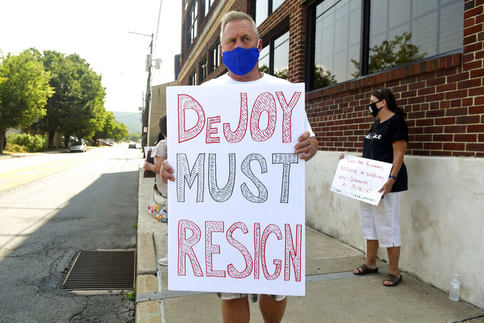 """Todd Zimmerman, of Mantzville, Pa., holds a sign """"DeJoy Must Resign"""" during a peaceful protest with the Schuylkill Democratic Action Group in front of the office of U.S. Rep. Dan Meuser, R-9, on Progress Avenue in Pottsville, Pa., on Thursday, Aug. 27, 2020. (Jacqueline Dormer/Republican-Herald via AP)"""