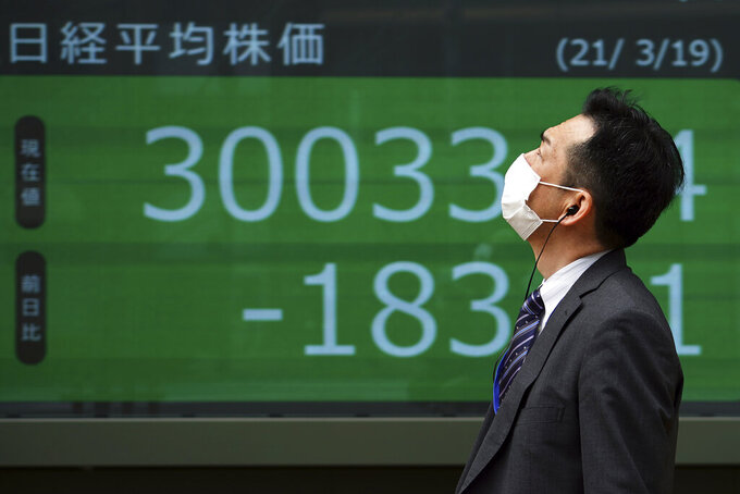 A man wearing a protective mask walks in front of an electronic stock board showing Japan's Nikkei 225 index at a securities firm Friday, March 19, 2021, in Tokyo. Asian stock markets followed Wall Street lower on Friday after rising U.S. bond yields pulled stocks lower, dampening enthusiasm driven by the Federal Reserve's promise of low interest rates. (AP Photo/Eugene Hoshiko)