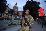 A member of the Georgia National Guard stands outside the State Capitol on Tuesday, July 7, 2020, in Atlanta. Georgia Gov. Brian Kemp mobilized the guard after a surge in violence over the weekend. (AP Photo/John Bazemore)