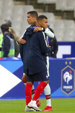 France's Kylian Mbappe and Portugal's Cristiano Ronaldo, left, greet each other at the end of the UEFA Nations League soccer match between France and Portugal at the Stade de France in Saint-Denis, north of Paris, France, Sunday, Oct. 11, 2020. (AP Photo/Thibault Camus)