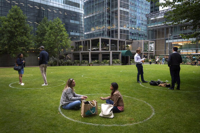 Drinkers stand within rings marked on the grass to maintain their social distance outside a bar in Canary Wharf, East London as further coronavirus lockdown restrictions are lifted in England, on Wednesday, July 1, 2020. (Victoria Jones/PA via AP)