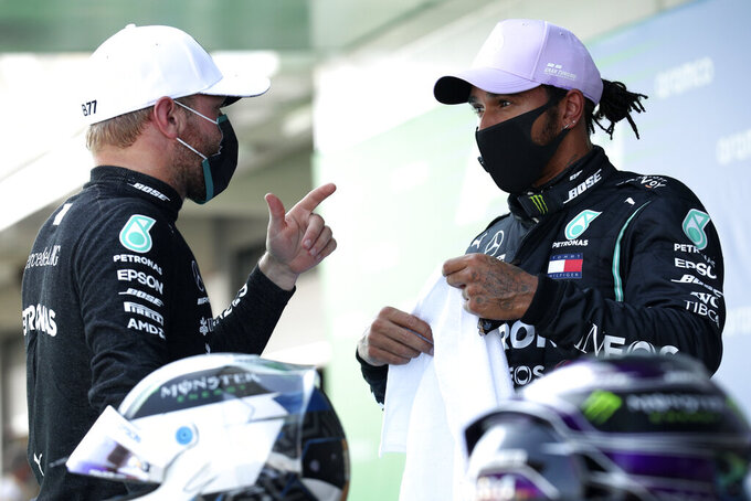 Mercedes driver Lewis Hamilton of Britain, right, talks to team mate Mercedes driver Valtteri Bottas of Finland after the qualifying prior to the Formula One Grand Prix at the Barcelona Catalunya racetrack in Montmelo, Spain, Saturday, Aug. 15, 2020. (Albert Gea, Pool via AP)